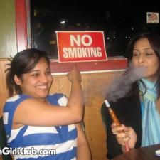 indian girl smoking at no smoking zone and showing the board